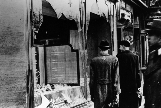 10th November 1938 - Three onlookers at a smashed Jewish shop window in Berlin following riots of the night of 9th November. - Photo courtesy: Hulton Archive/Getty Images