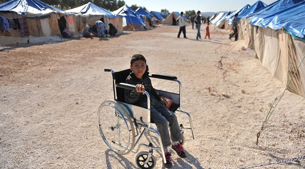 A Syrian boy on a wheelchair in Qah refugee camp. A UN report notes child casualty rates in Syria are the highest recorded - Photo Bulent Kilic AFP