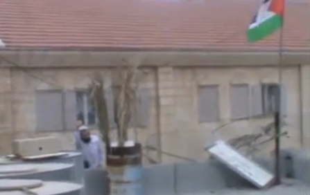 Settler caught climbing on Arab's roof to remove Palestinian flag - screenshot