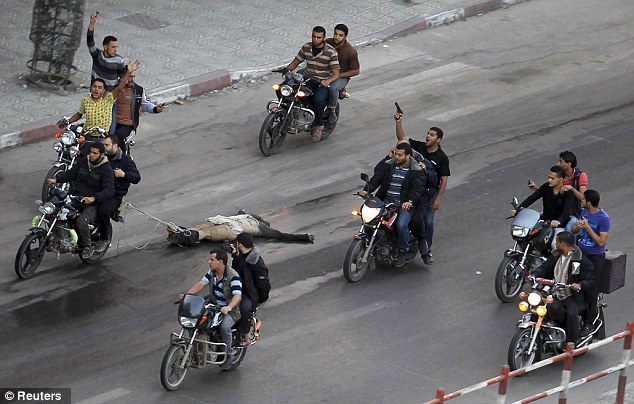 Paraded - Palestinian gunmen ride motorcycles as they drag the body of a man, who was suspected of working for Israel  20 November 2012