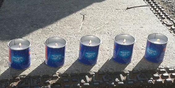 Memory candles to honor the 5 victims of terror.