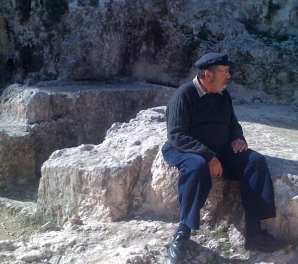 Dr. Gabriel Barkay at Ketef Hinnom, sitting on top of the cave where he discovered the Silver Scrolls, two silver amulets that contain the Priestly Benediction from the Book of Numbers. - Wikimedia Commons