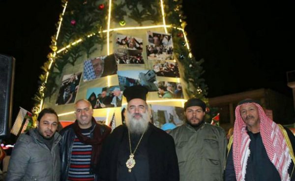 Theophilos & visitors with the 2016 martyr's Christmas tree in eastern Jerusalem. - Screenshot Israel TV2 News